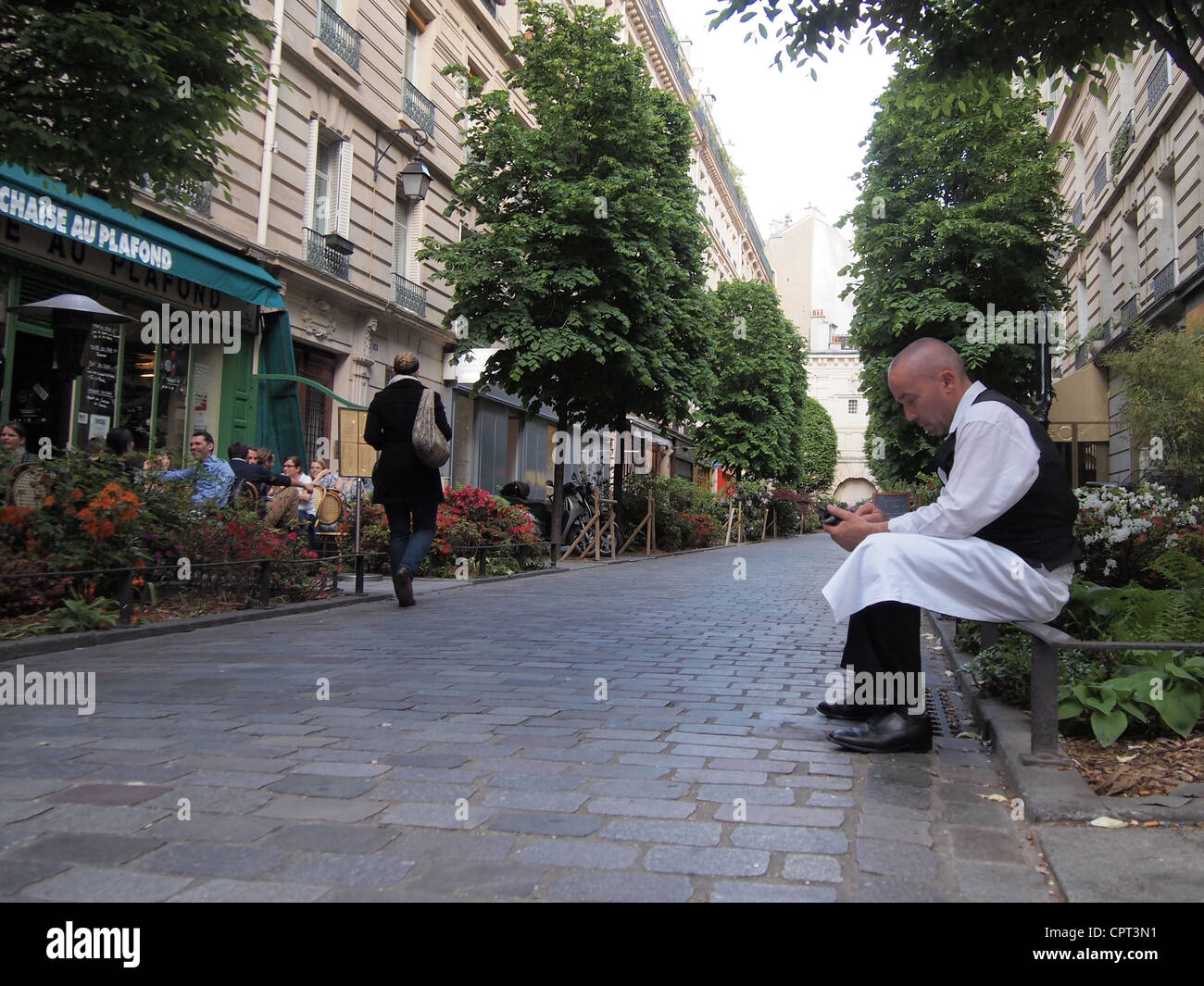 French waiter takes a break to check messages on his Smartphone, Paris, France, May 9, 2012, © Katharine Andriotis - Stock Image