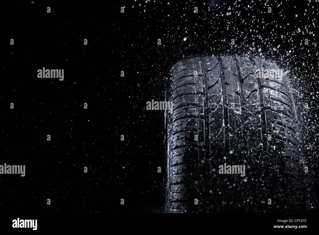 New car tire in rain. - Stock Image