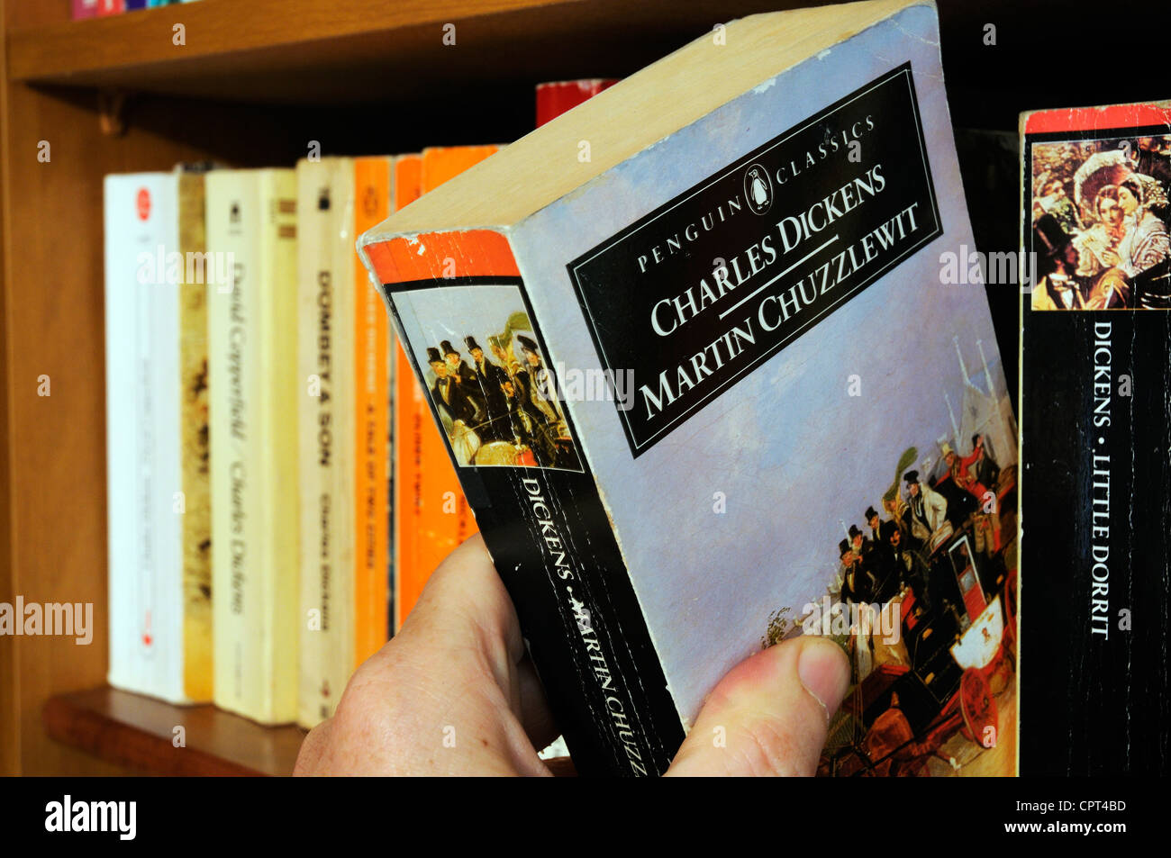 A hand taking Charles Dickens Martin Chuzzlewit  from a bookshelf - Stock Image