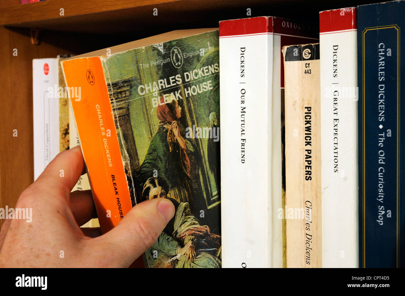 A hand taking Charles Dickens Bleak House from a bookshelf - Stock Image