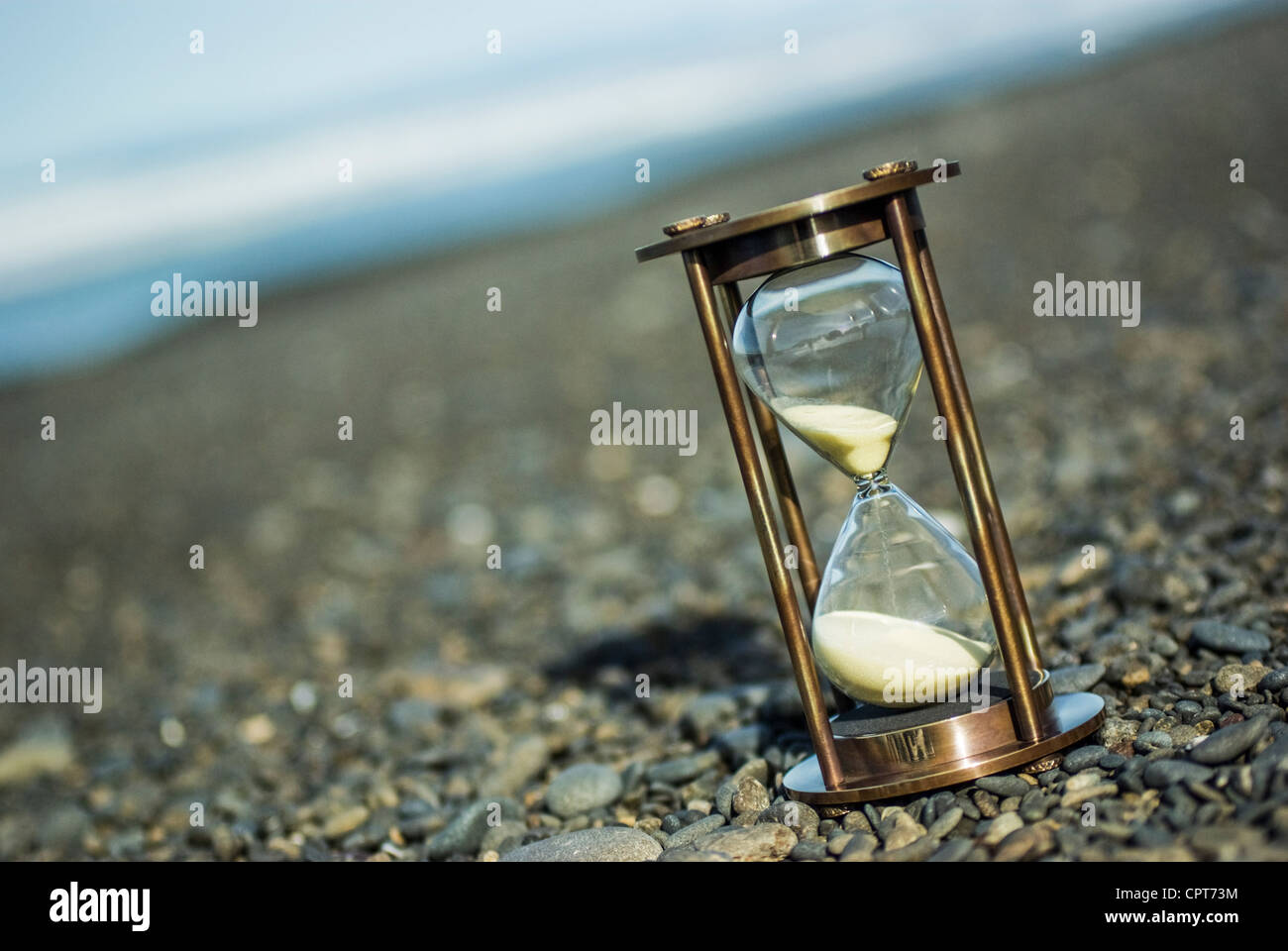 Hourglass on stony beach, photographed at an angle. - Stock Image