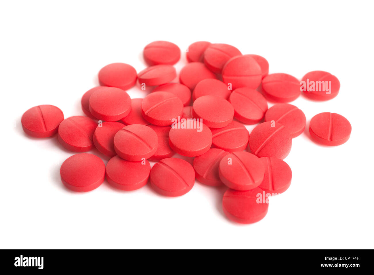 Pile of red pills on a white background. - Stock Image