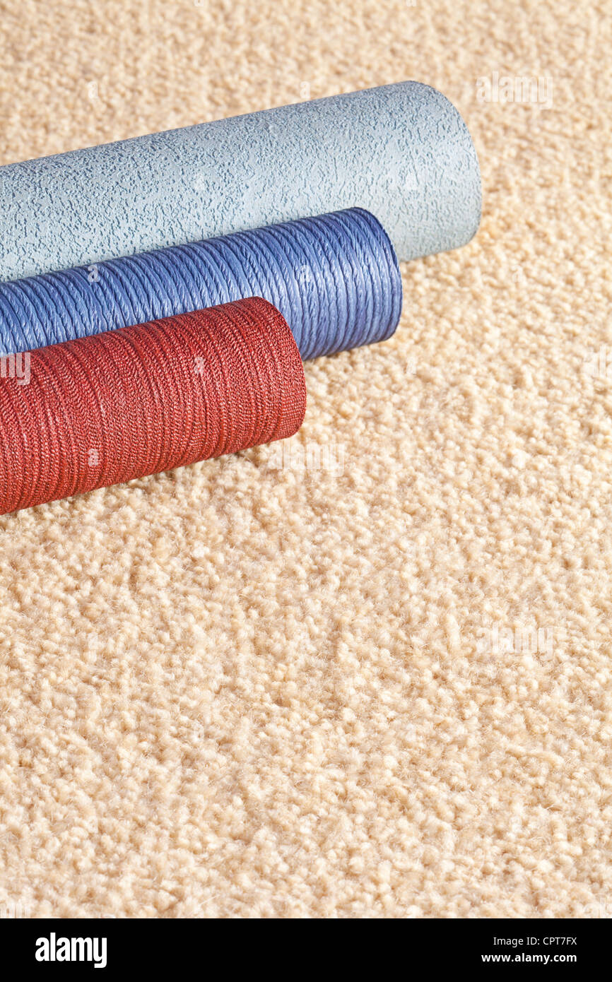 Sample rolls of wallpaper on a light coloured carpet, with copy space. - Stock Image