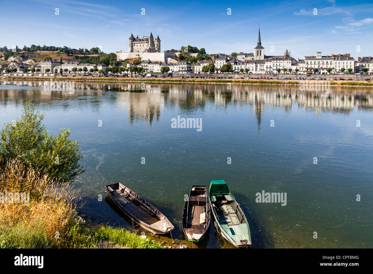 The town of Saumur reflecting in the River Loire on a sunny summer morning. - Stock Image