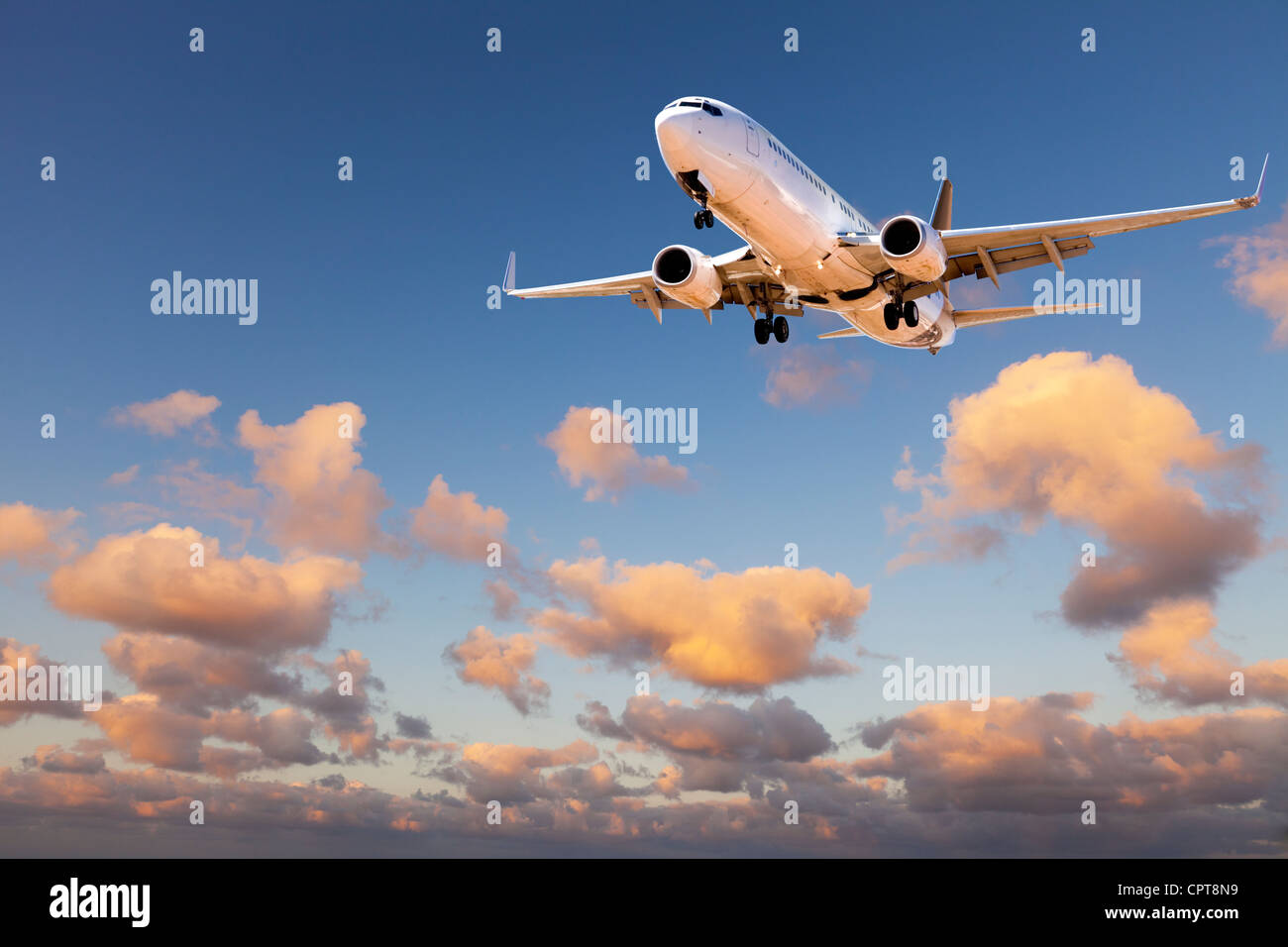 Boeing 737 coming in to land in sunset sky. - Stock Image