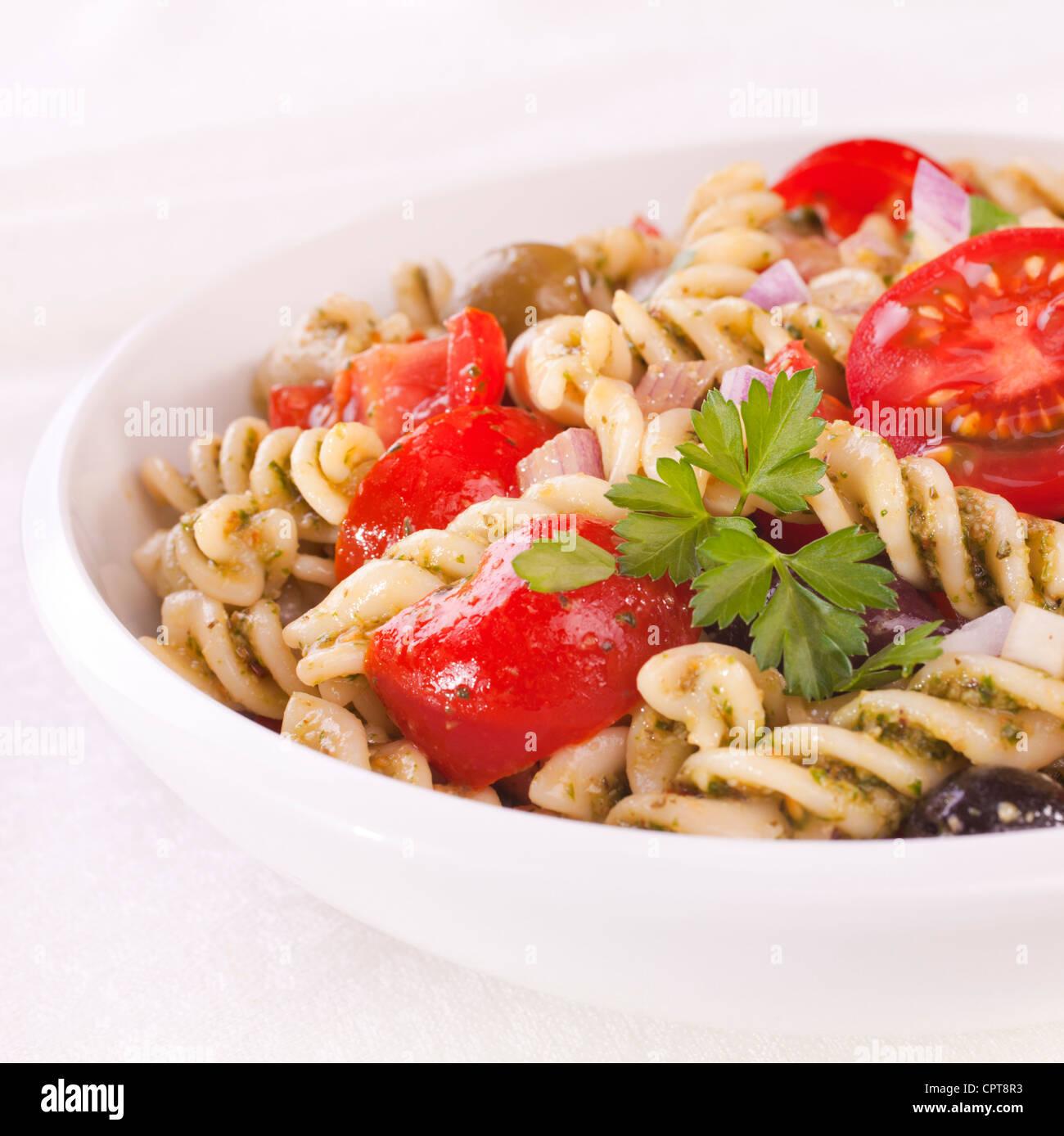 Fusili pasta salad, with rocket pesto, juicy tomatoes, olives and onion. - Stock Image