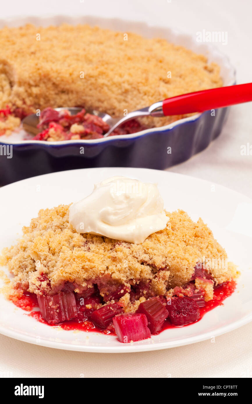 A plate of rhubarb and raspberry crumble with a dollop of cream, serving dish and spoon in the background. - Stock Image
