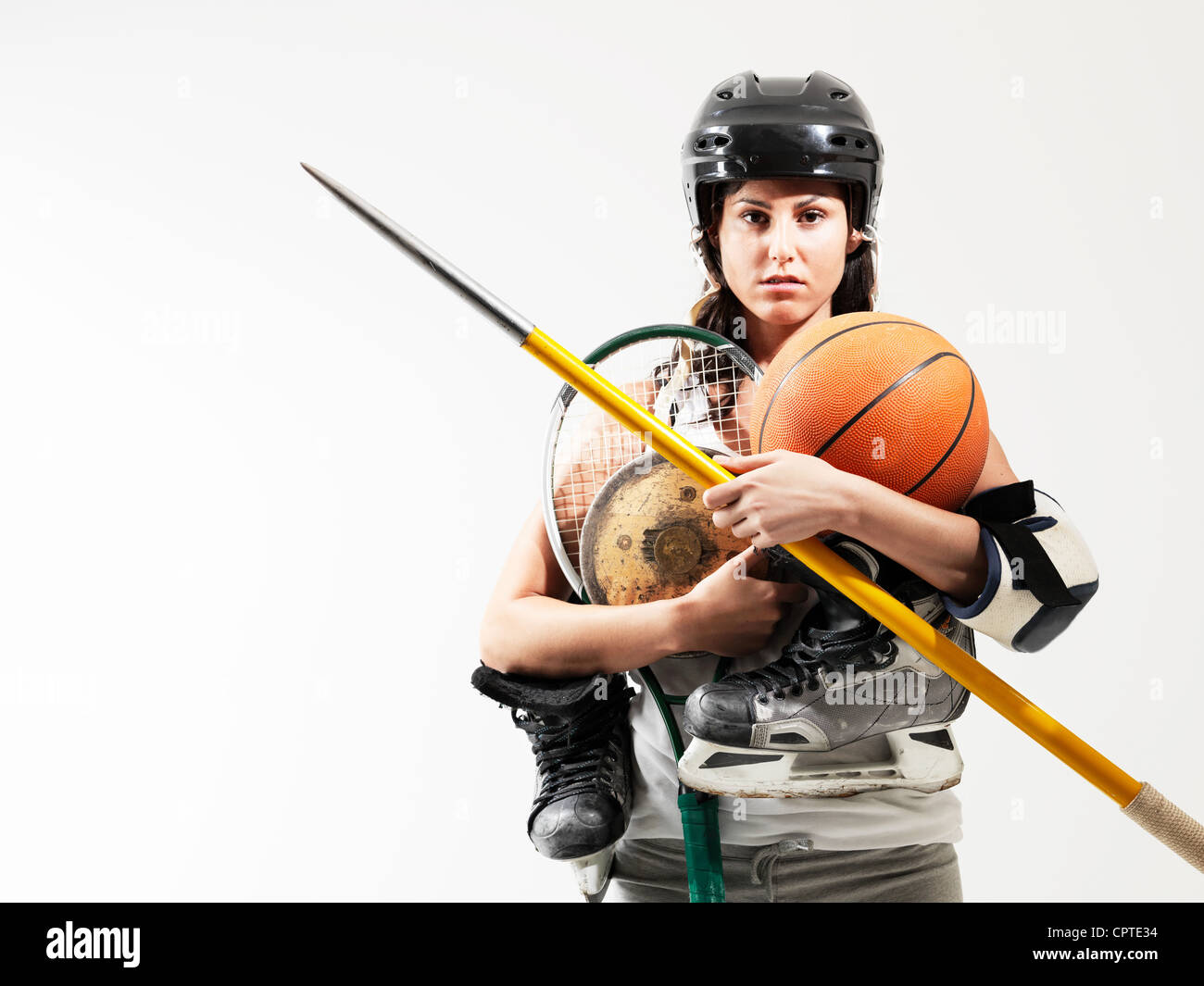 Young woman holding sports equipment against white background - Stock Image