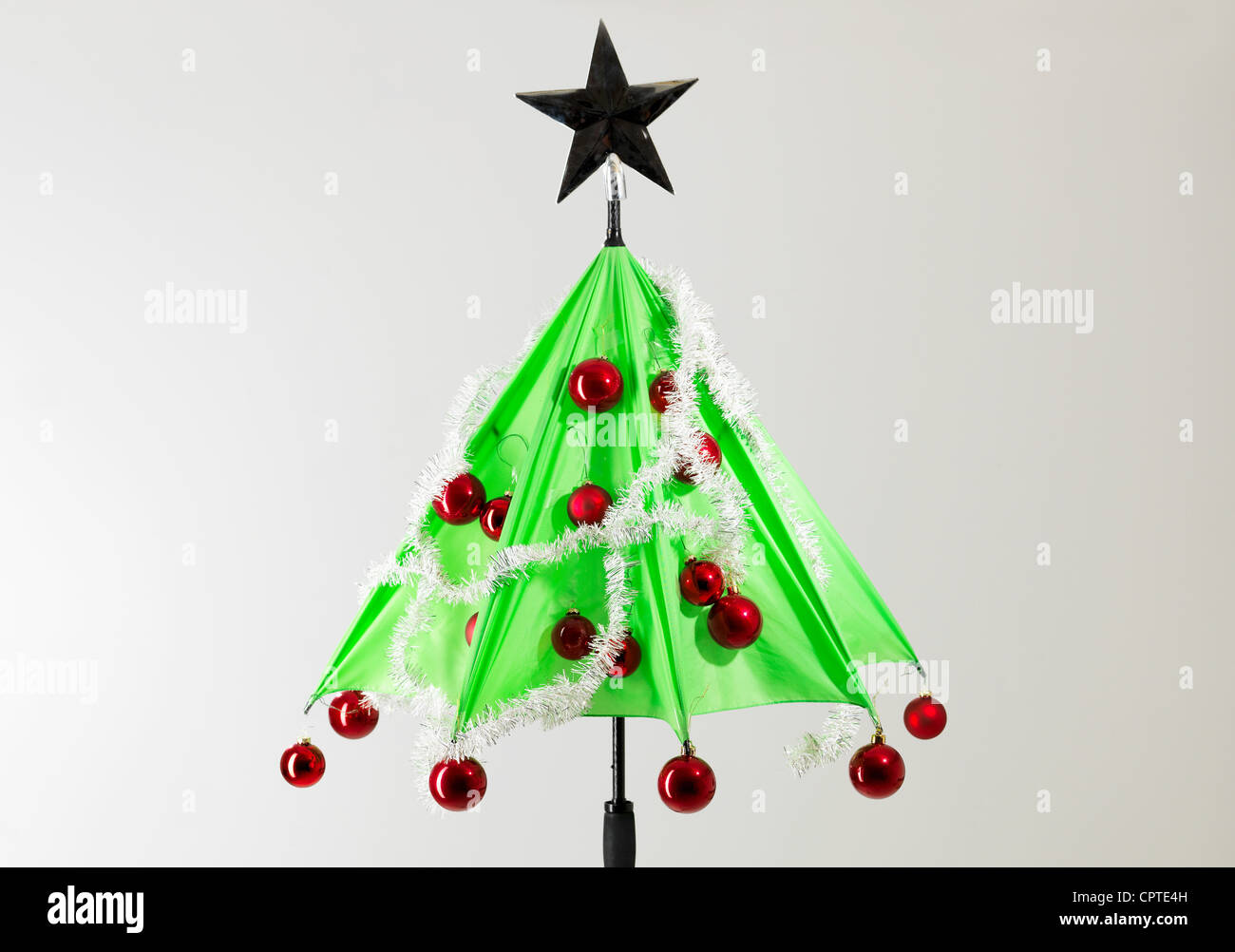Green umbrella with Christmas decorations against white background - Stock Image