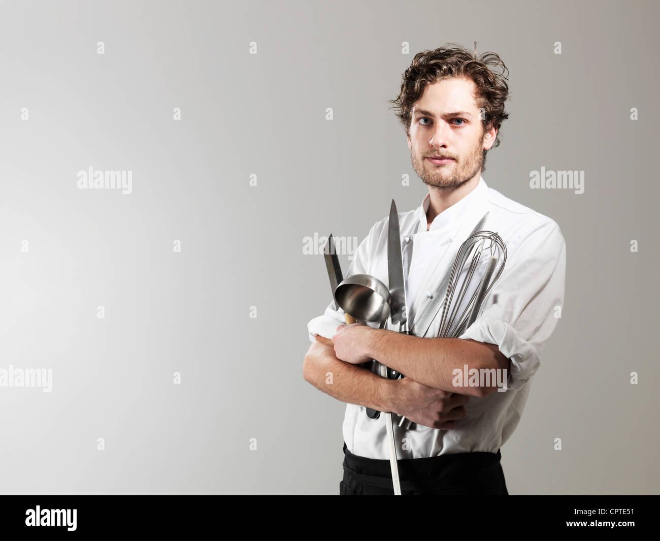 Chef holding kitchen utensils against white background - Stock Image