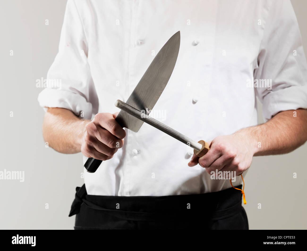Chef sharpening knife against white background - Stock Image
