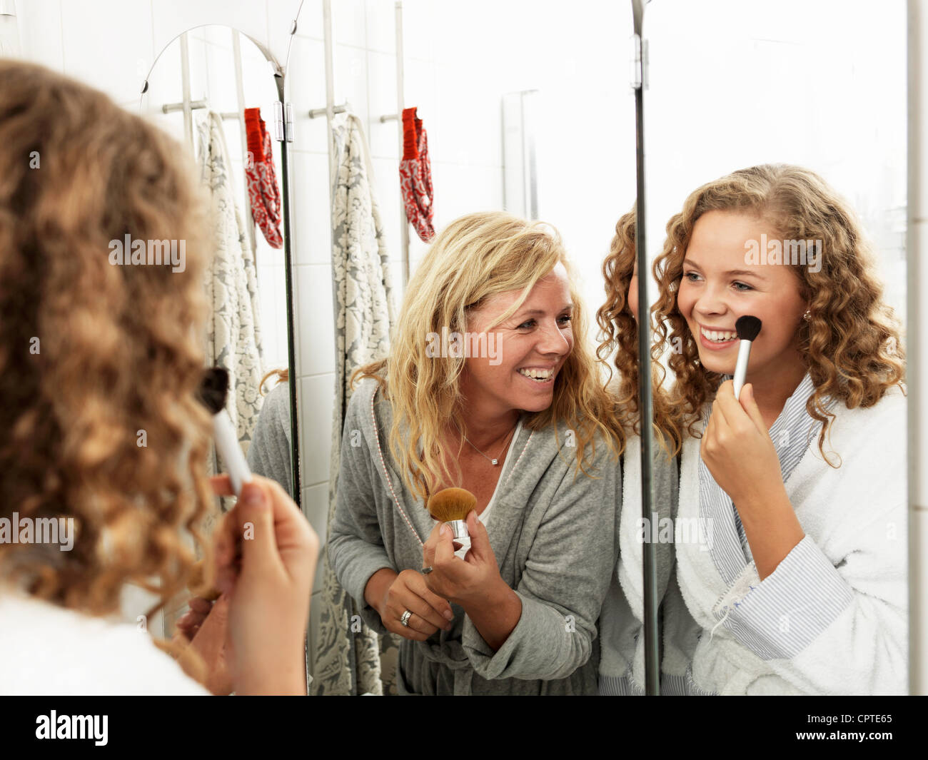 Mature woman applying make-up with daughter in mirror - Stock Image