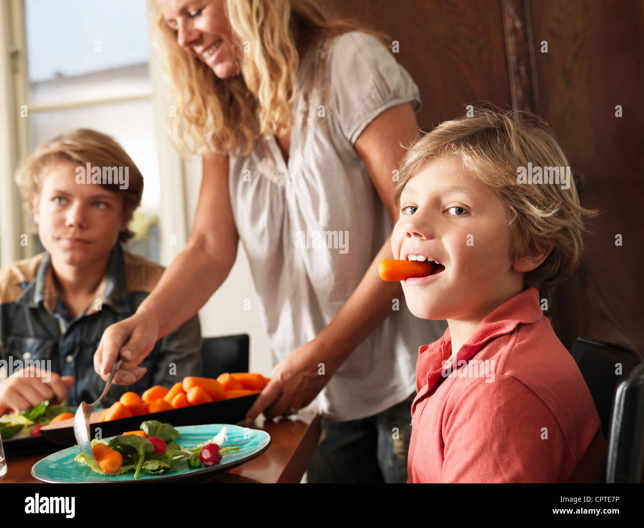 Boy holding carrot in his mouth as mother serves healthy meal - Stock Image