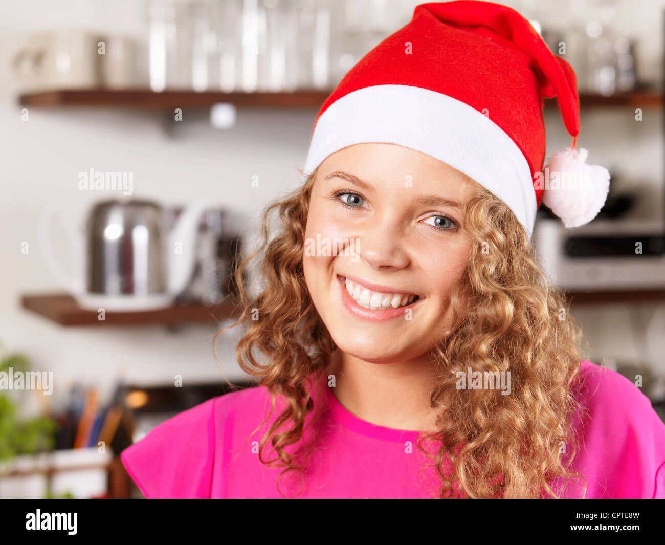 Portrait of young woman wearing Santa hat, smiling - Stock Image