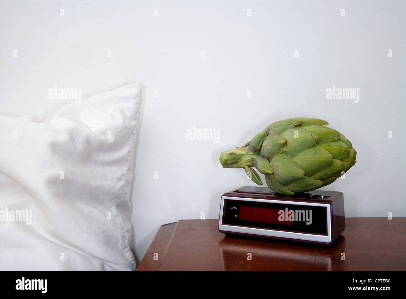 Artichoke on alarm clock - Stock Image