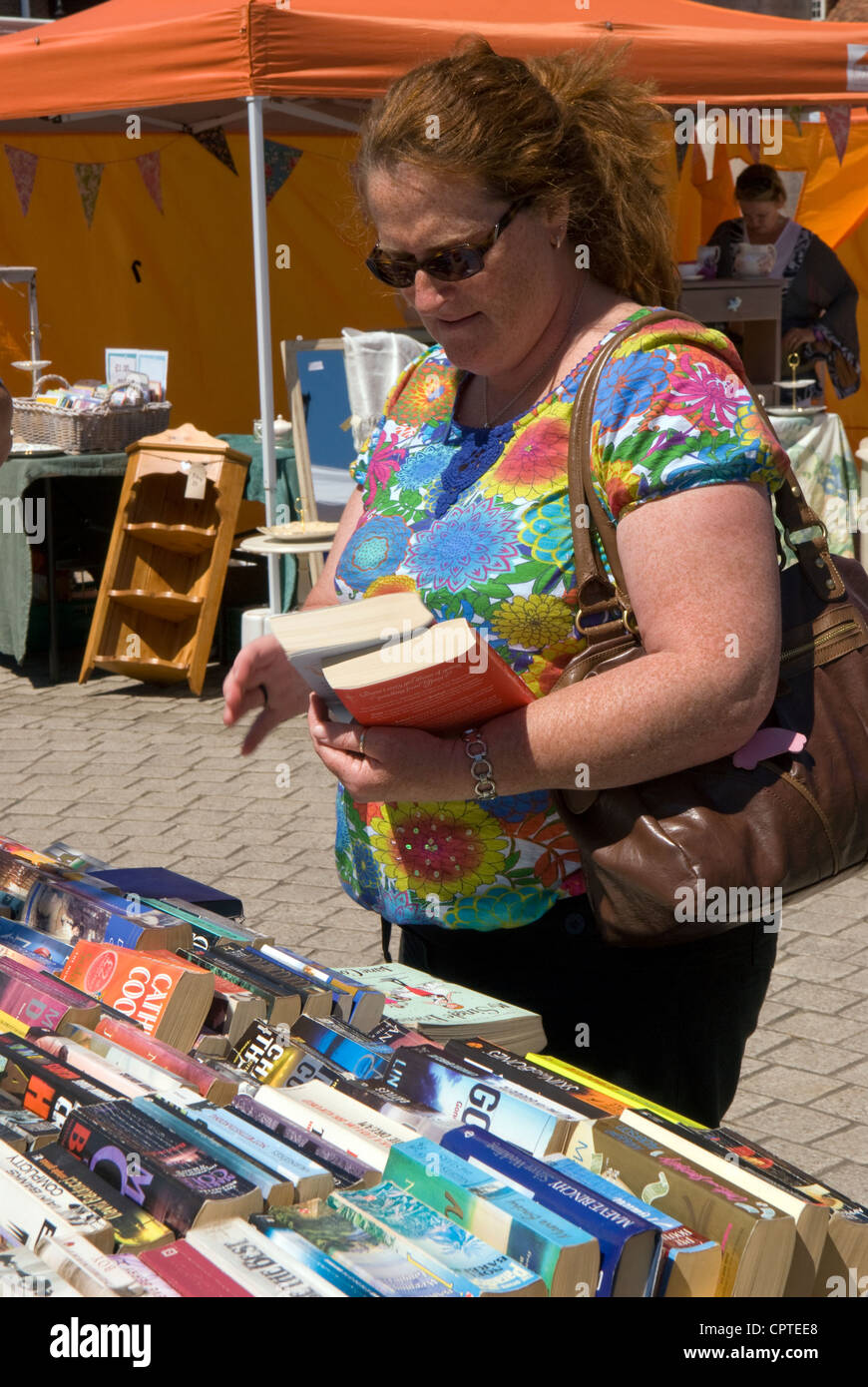Woman perusing book stall at the weekly outdoor market, Petersfield, Hampshire, UK. - Stock Image