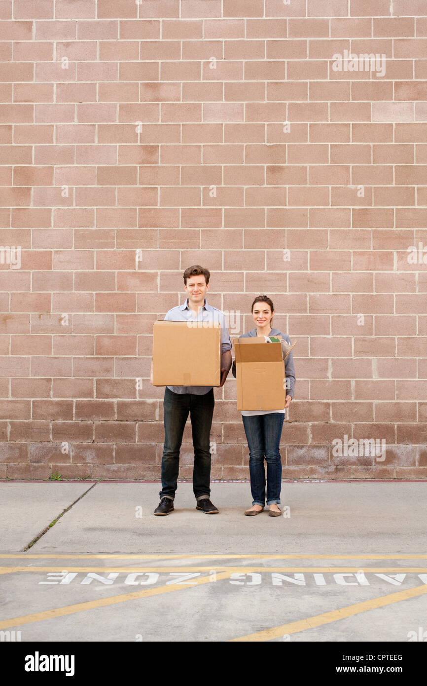 Portrait of young couple holding cardboard boxes in loading bay - Stock Image