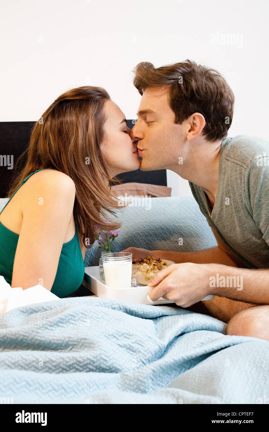 Young couple kissing over breakfast tray - Stock Image