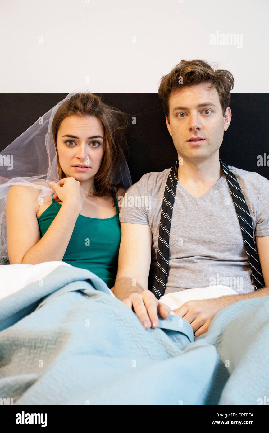 Portrait of young newlywed couple lying in bed - Stock Image