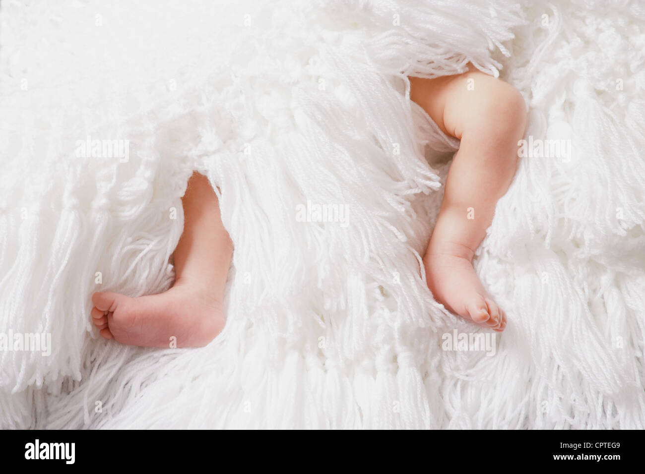 Baby boy's legs on white blanket - Stock Image