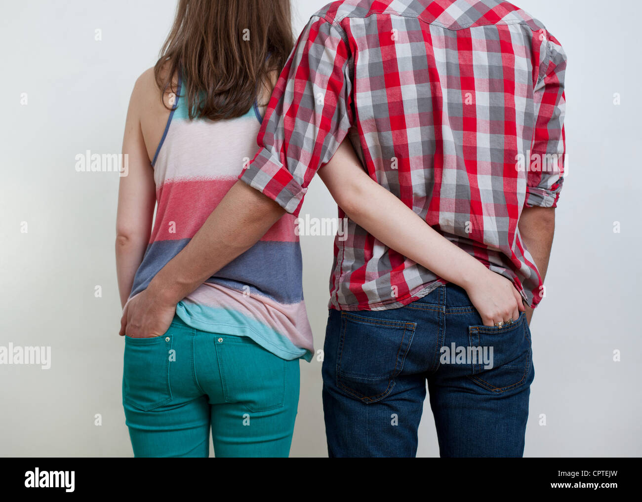Young couple with hands in each other's back pockets - Stock Image