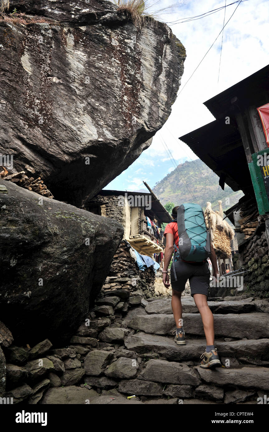 Woman trekking on stone pathway, Jagat, Nepal - Stock Image