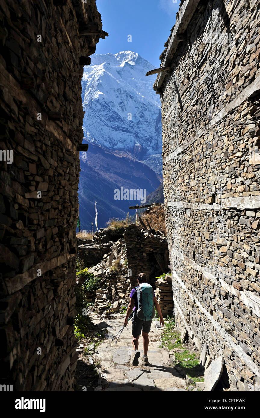 Woman treks through medieval stone buildings, Ghyaru, Nepal - Stock Image