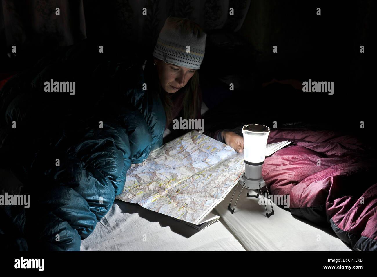 Woman in sleeping bag, looking at trail map, Yak Kharka, Nepal - Stock Image