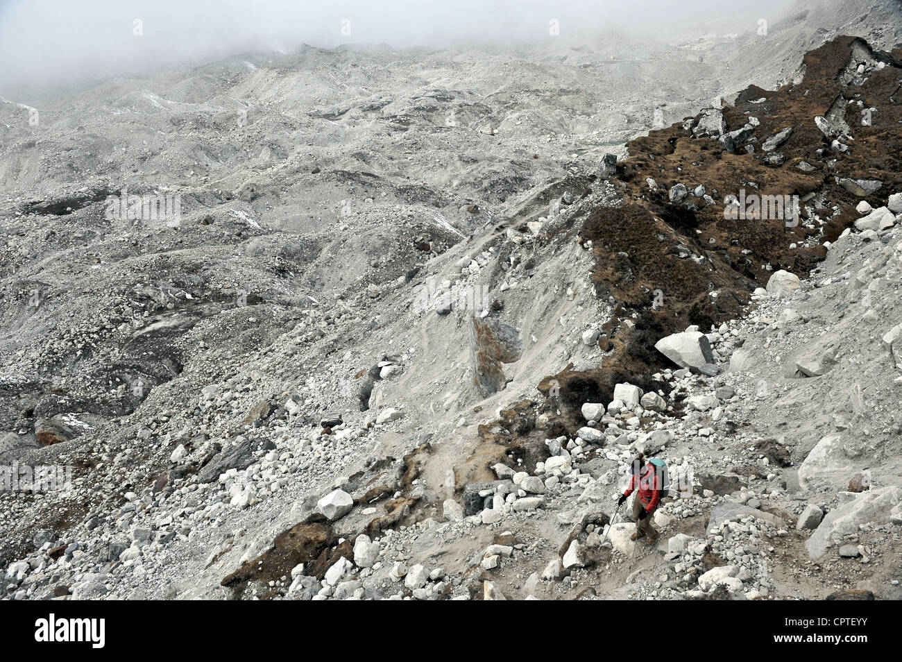 Female trekker descending across the moraine of the Nguzumpa Glacier, Nepal - Stock Image
