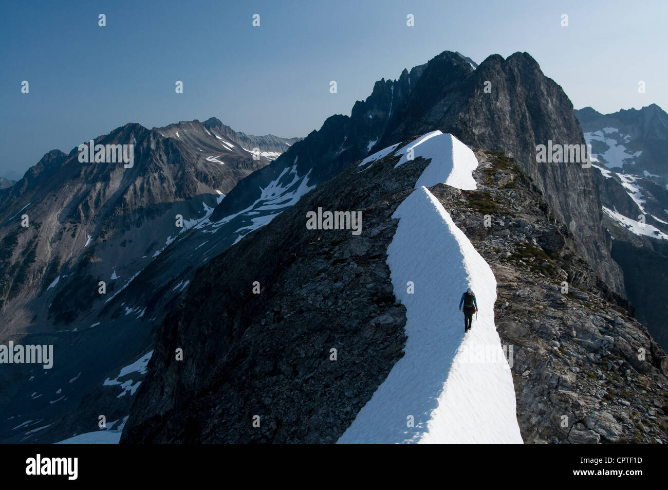 Female climber traversing snowy ridge, Redoubt Whatcom Traverse, North Cascades National Park, WA, USA - Stock Image