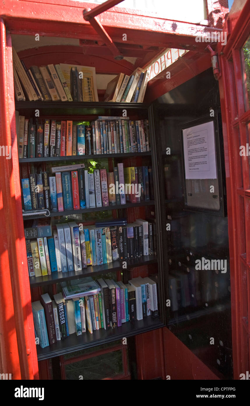 Old red telephone box used as village book exchange - Stock Image