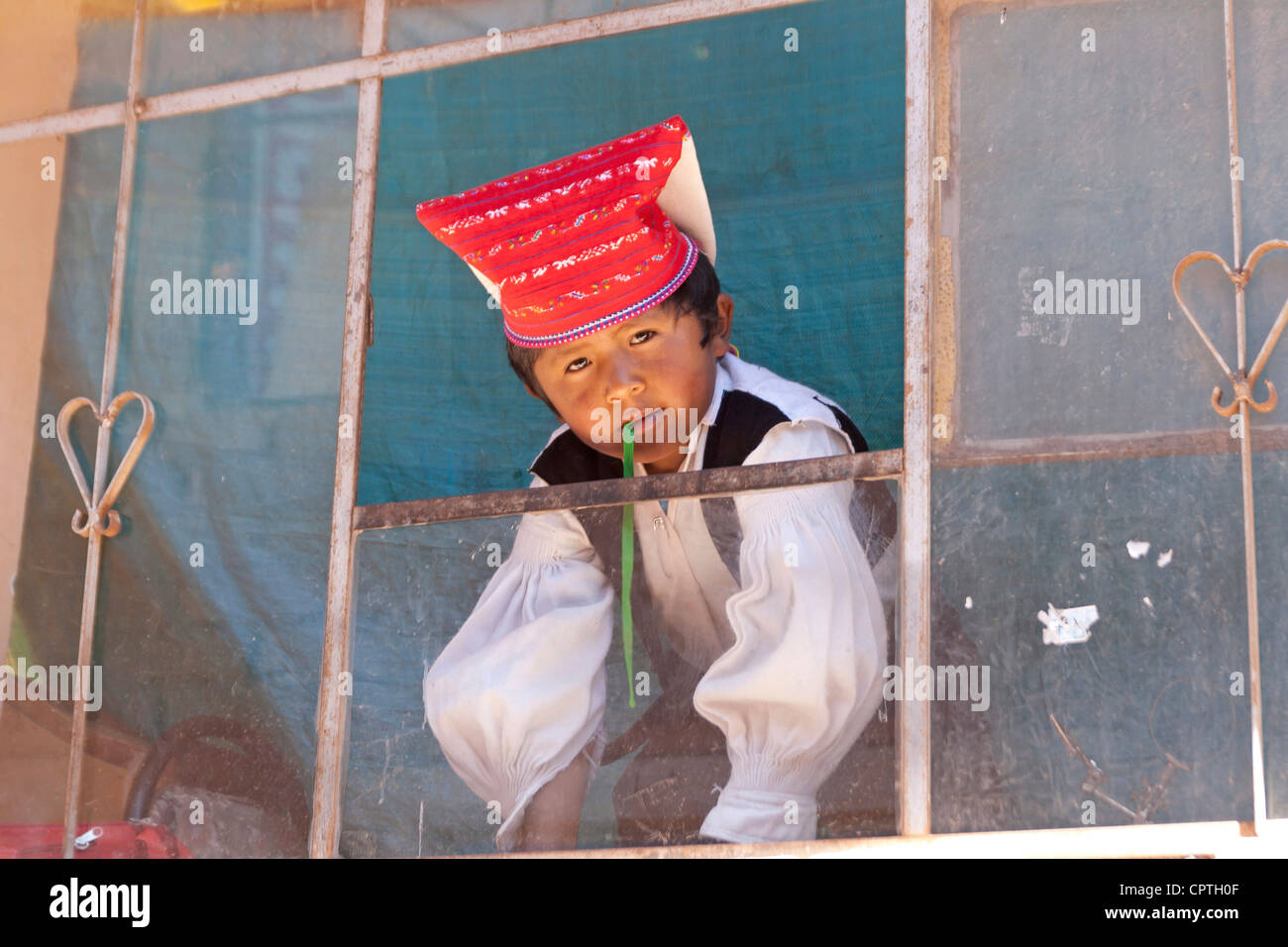 Lake Titikaka, Taquile island, Peru, child looking out of the window in celebrational attire - Stock Image