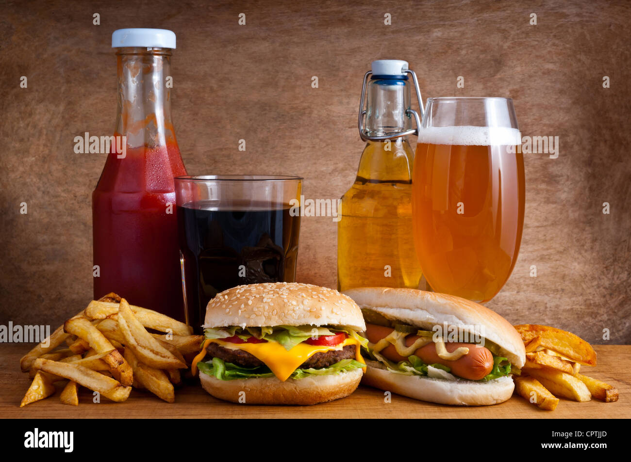 Junk food with burger, hotdog, french fries, cola, ketchup and beer on a wooden background - Stock Image