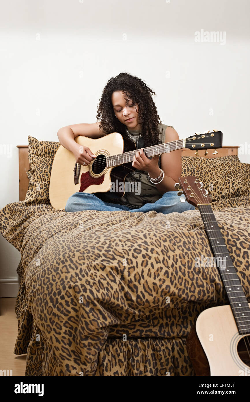 Young woman sat on a bed playing guitar - Stock Image