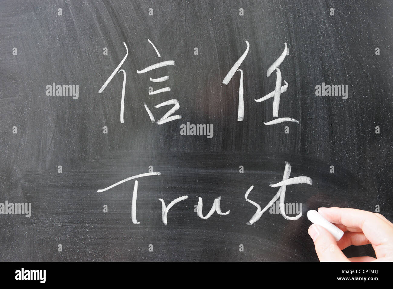 Trust word in Chinese and English written on the chalkboard - Stock Image