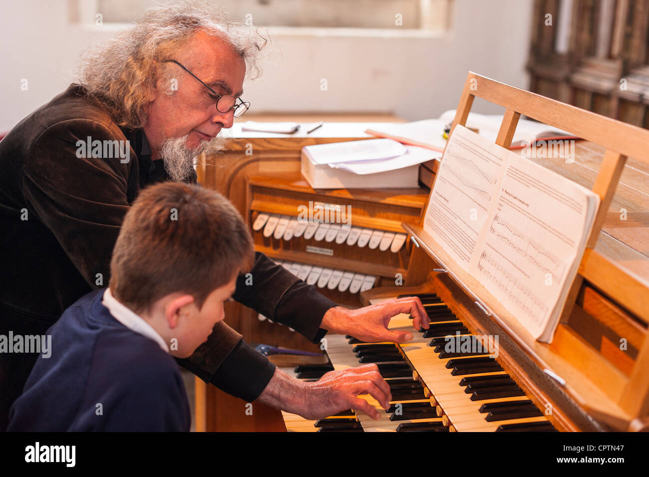 A 12 year old boy having tuition on playing a church organ in the Uk - Stock Image