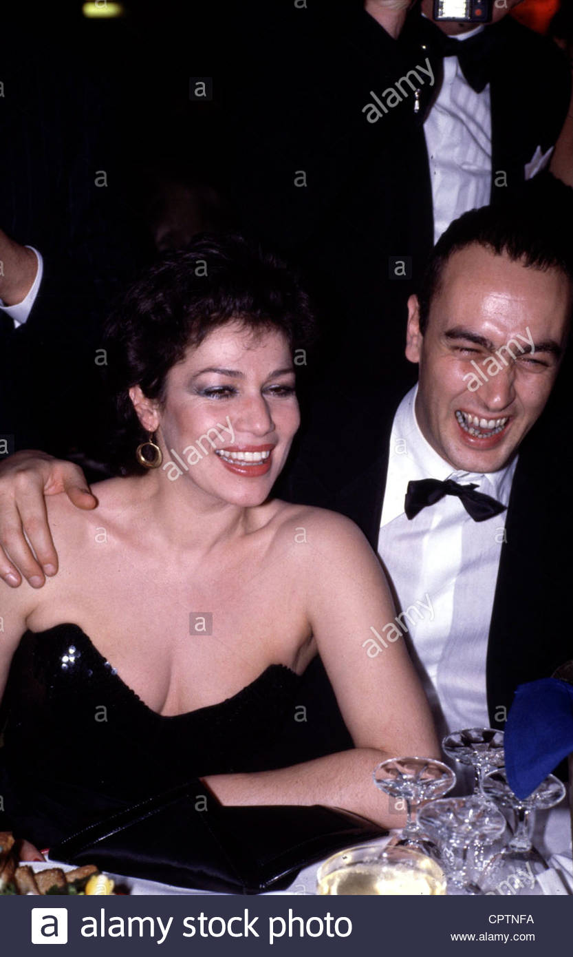 Eichinger, Bernd, 11.4.1949 - 24.1.2011, German producer, half length, 1980s, sitting at table, cleavage, laughing, - Stock Image
