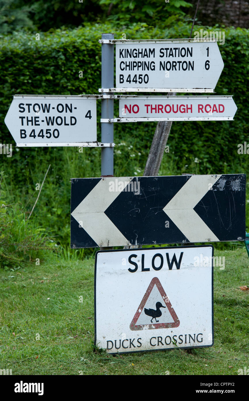 Slow Ducks crossing sign next to a road sign. Kingham, Oxfordshire, Cotswolds , England Stock Photo
