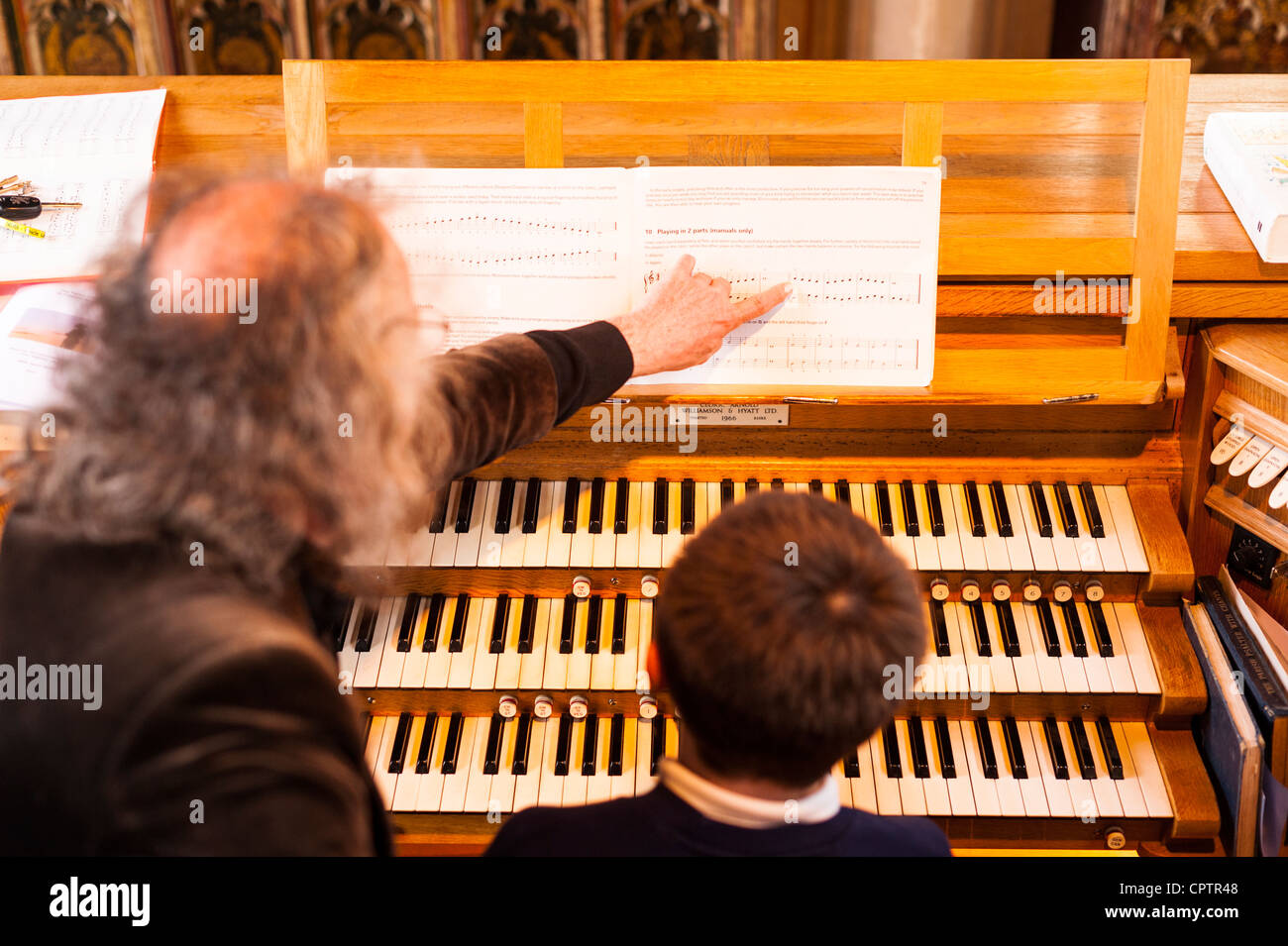 A 12 year old boy having tuition on playing a church organ with point of focus on the music in the Uk - Stock Image