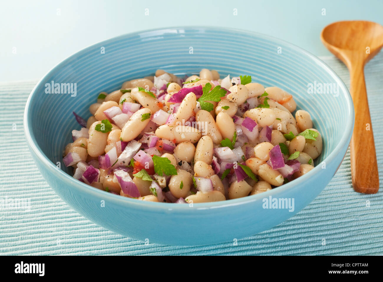 Italian cannelini bean salad of beans in lemon vinaigrette with red onion, rosemary, parsley and garlic. - Stock Image