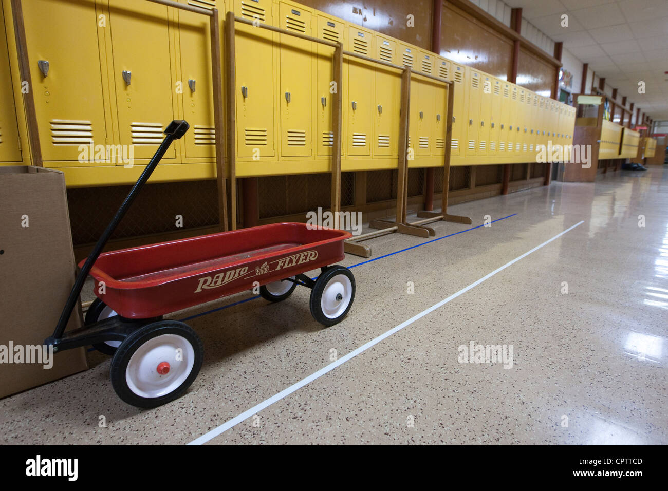 A red wagon stands in an empty hallway of a middle school closed for the summer in Texas - Stock Image