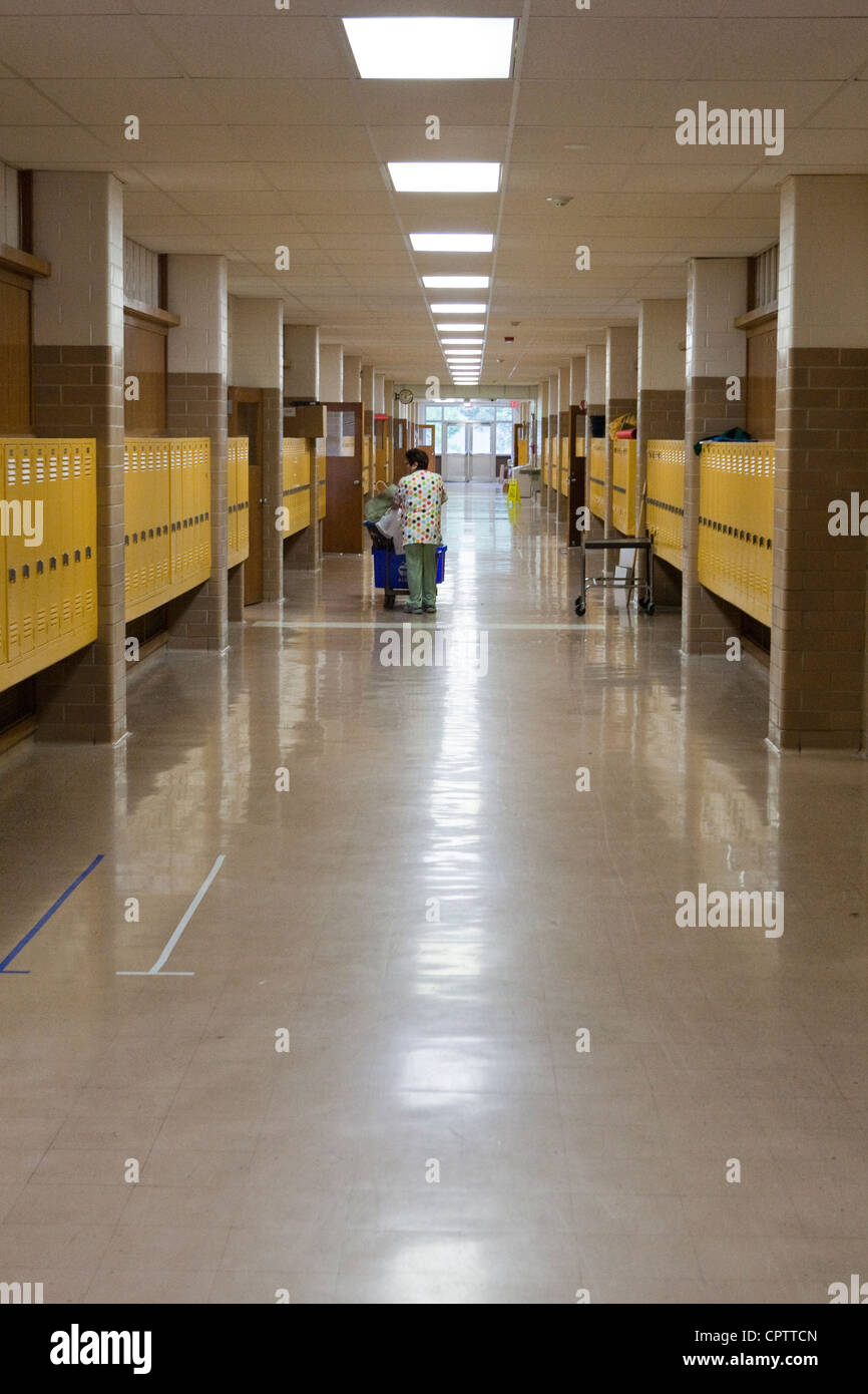 A lone custodian walks down a hallway of a middle school in Texas that is closed for the summer. - Stock Image
