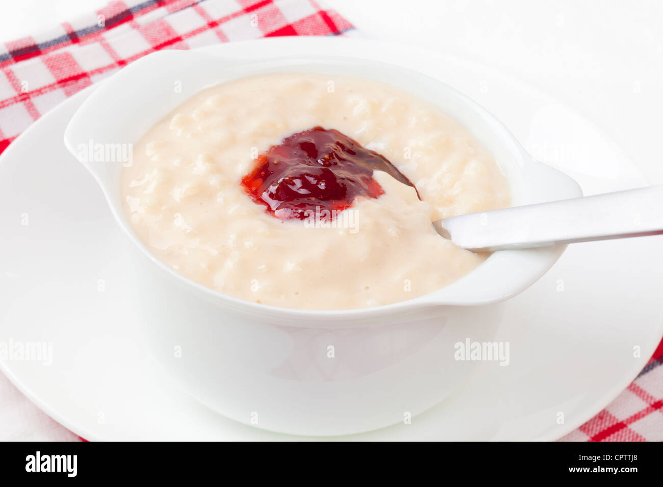 A bowl of rice pudding topped with strawberry jam, spoon digging in. - Stock Image