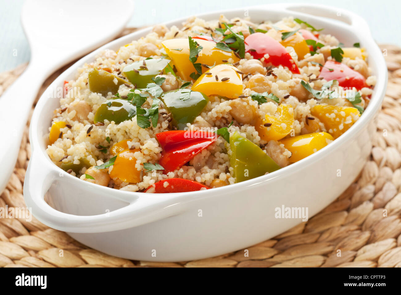 Couscous with chickpeas, red, green and yellow peppers, onion, cumin seeds and parsley, cooked with extra virgin - Stock Image