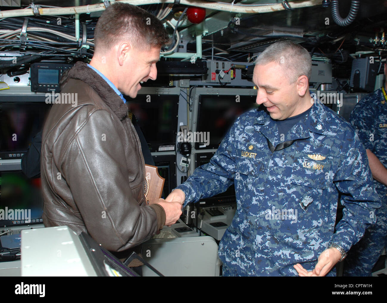 Assistant Secretary of the Navy Juan M. Garcia III shakes hands and exchanges command coins with Cmdr. Michael Luckett, - Stock Image