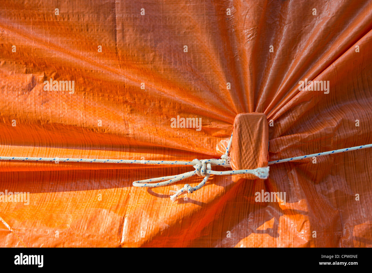 Knot, securing an orange cover sheet - Stock Image