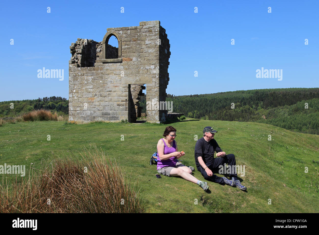 Mature couple of walkers rest at Skelton Tower, North Yorkshire Moors, England - Stock Image