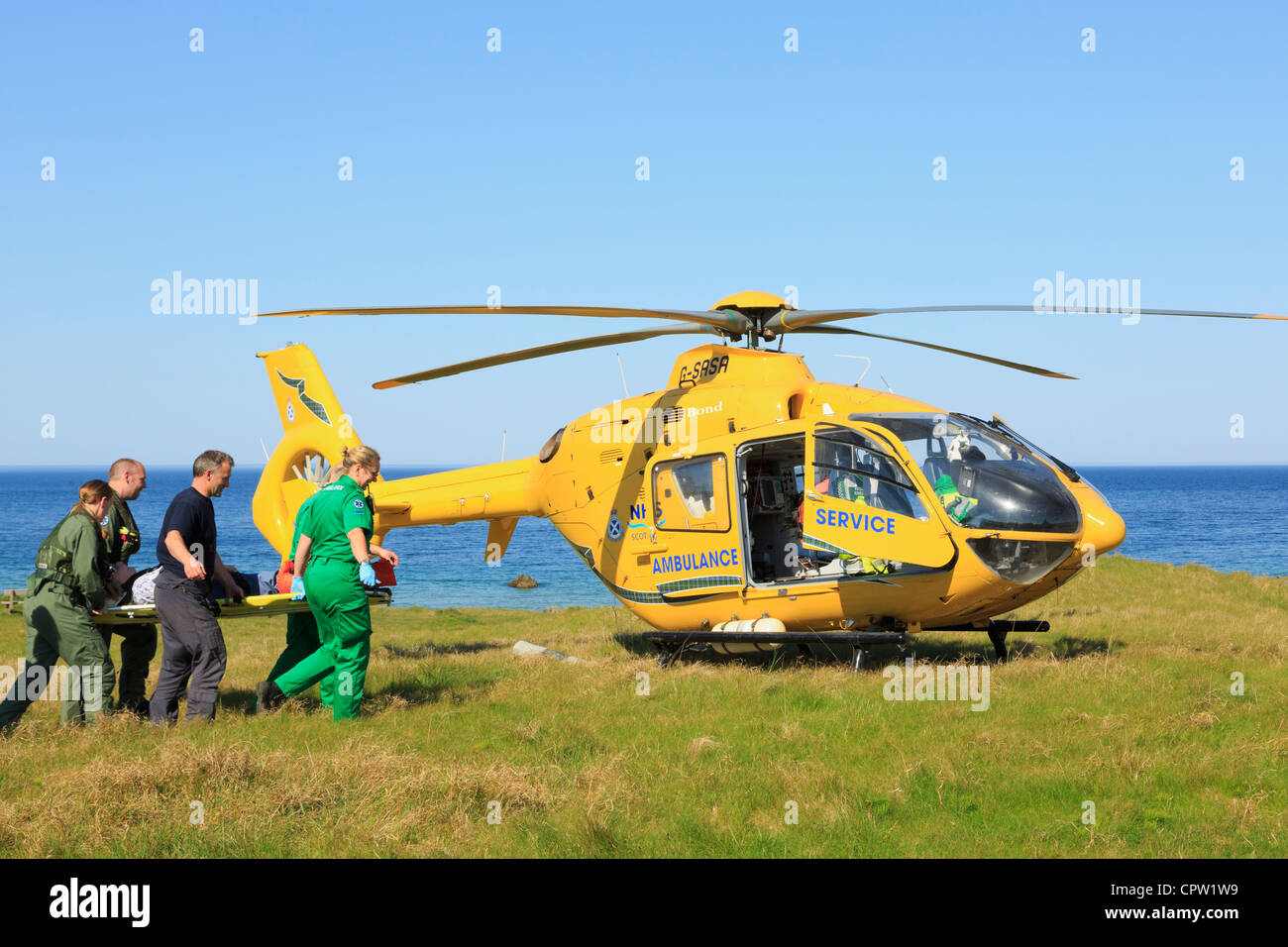 UK Scottish Air Ambulance Service Helicopter paramedics rescuing a woman on a stretcher on the remote North West - Stock Image