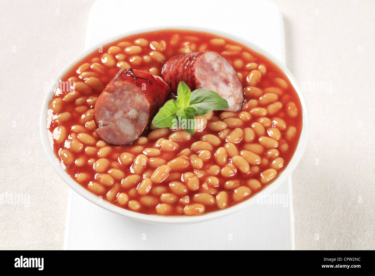 Beans and sausage with red sauce in a white bowl - Stock Image