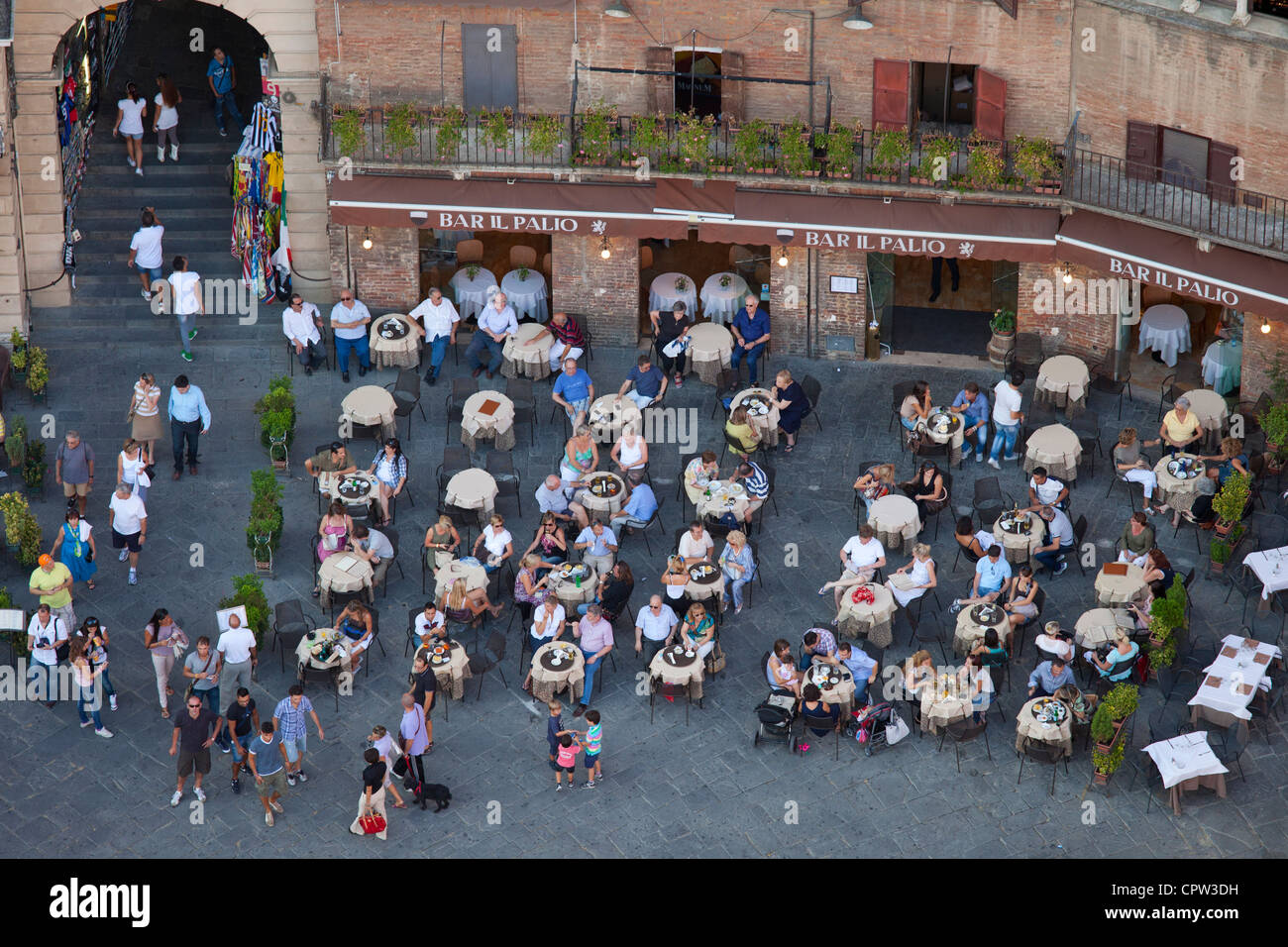 Aerial view from Il Torre, clock tower of diners at Bar Il Palio in Piazza del Campo, Siena, Italy - Stock Image